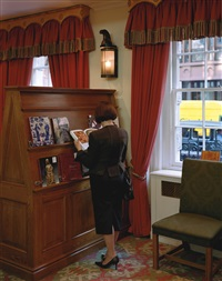 a woman consulting a catalogue by jeff wall