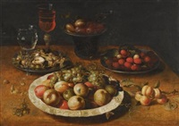 a still life of apples and grapes in a blue-and-white porcelain bowl, raspberries and walnuts in pewter dishes, plums on a pewter dish atop a stand, together with three wine-glasses and sprigs of apricots and gooseberries upon a wooden table by osias beert the elder