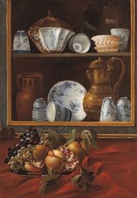 un piatto di frutta posto davanti una dispensa quasi in forma di trompel'oeil contenente vasellame di vario tipo e liquori, (+ another similar; pair) by cristoforo munari