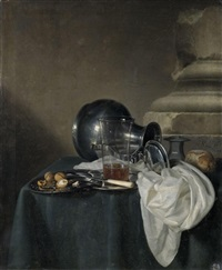 a still life with a pewter jug on its side, a glass of beer and walnuts on pewter dishes, all arranged on a table draped with a green cloth by simon luttichuys