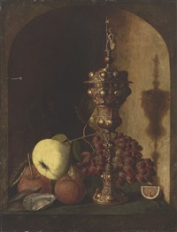 grapes, a pear, an apple, a lemon, oysters and a silver-gilt cup in a stone niche by pieter van den bos