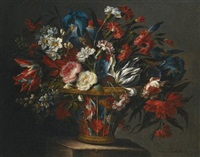 still life with flowers, including roses, narcissi, peonies, blue irises and variegated tulips, in a wicker basket set upon a stone plinth by juan de arellano