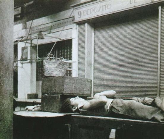 Homme couché sur le dos dormant devant le rideau de fer dun magasin ...