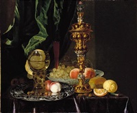 a still life of peaches, grapes, a lemon, a segment of orange, hazelnuts and a bread roll, together with a roemer, a large gold pronckblokaal and a silver platter, all laid out on a draped table by simon luttichuys
