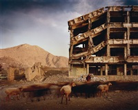 bullet-scarred apartment building and shops in the karte char district of kabul by simon norfolk