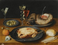 a still life of a roast chicken, a ham and olives on pewter plates with a bread roll, an orange, wineglasses and a rose on a wooden table (collab. w/studio) by osias beert the elder