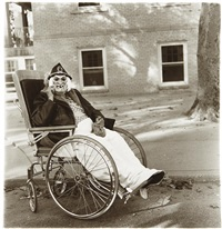 masked woman in wheelchair, p.a by diane arbus