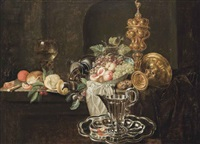 an orange, bread and a knife, with a partly peeled lemon and cherries on a silver tray, peaches, grapes and a medlar in a porcelain bowl, with an upturned tazza and a silver guilt cup and cover, on a partly draped and a jug on a tray by simon luttichuys