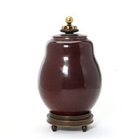 a stoneware lid vase decorated with oxblood glaze by knud andersen