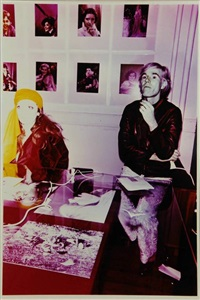 andy warhol sitting behind a desk by billy name