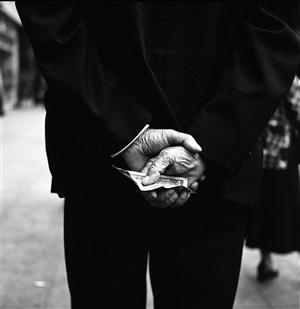untitled (hands behind back, dollar bill) by vivian maier
